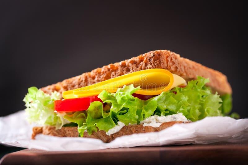 Bocadillo tostado con las hojas, los tomates y el queso de la ensalada con la bifurcación en una tabla de cortar en un fondo verd foto de archivo