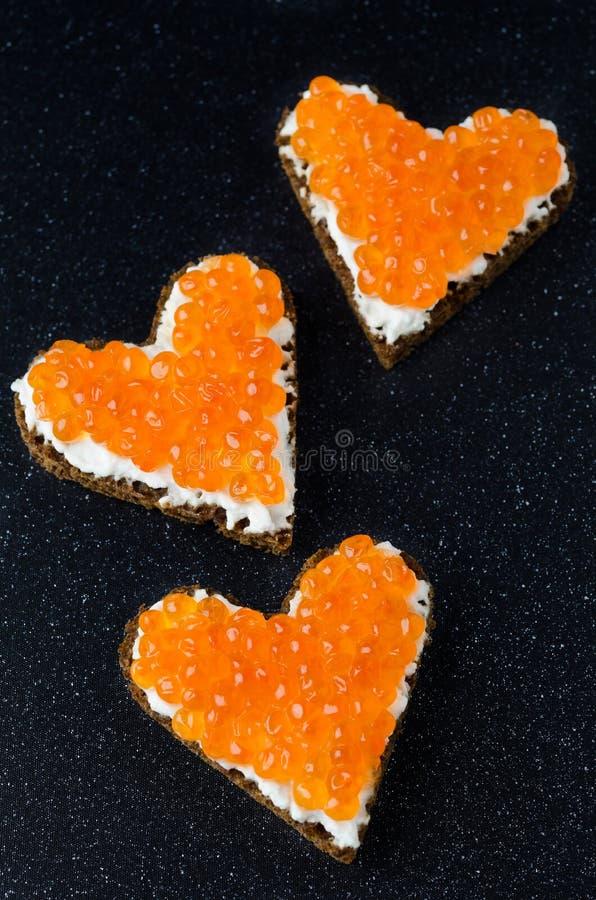 Bocadillo tres con el caviar rojo bajo la forma de corazón en un negro imagen de archivo