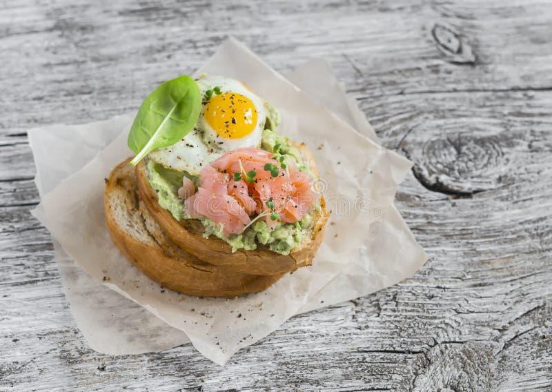Bocadillo triturado del aguacate con el salmón ahumado y el huevo de codornices frito Un desayuno o un bocado delicioso imagenes de archivo