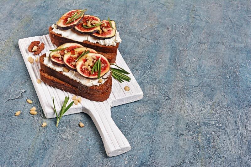 Bocadillo vegetariano con los higos, el queso suave, la miel, la nuez y el romero en el tablero de madera blanco imagenes de archivo