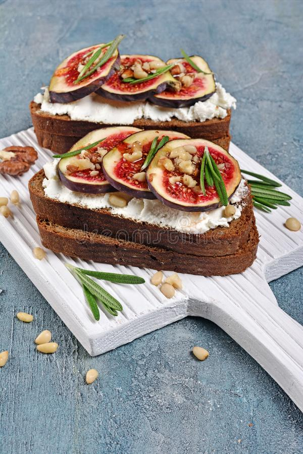 Bocadillo vegetariano con los higos, el queso suave, la miel, la nuez y el romero en el tablero de madera blanco imágenes de archivo libres de regalías
