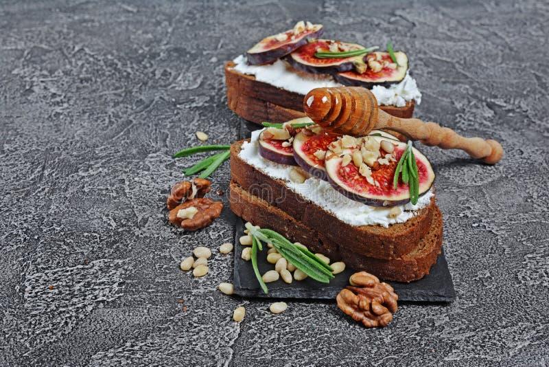 Bocadillo vegetariano con los higos, el queso suave, la miel, la nuez y el romero en tablero negro de la pizarra imagen de archivo libre de regalías