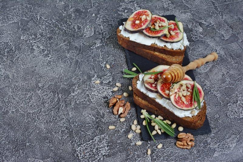 Bocadillo vegetariano con los higos, el queso suave, la miel, la nuez y el romero en tablero negro de la pizarra fotografía de archivo libre de regalías