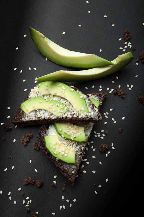 Bocadillo vegetariano del pan negro con las rebanadas de aguacate, el queso derretido y el sésamo fotos de archivo libres de regalías
