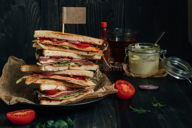 Bocadillo y salsas sabrosos frescos de club en la tabla oscura de madera foto de archivo