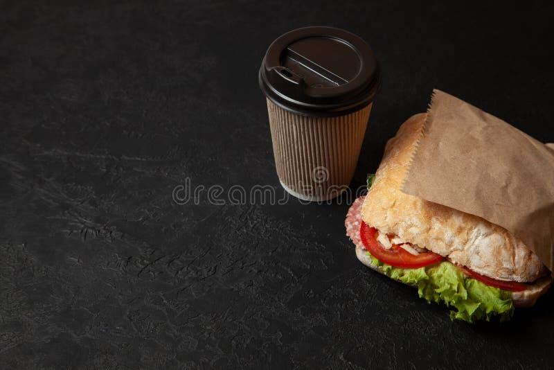 Bocadillo y taza de café en fondo negro Desayuno o bocado de la mañana cuando está hambriento Comida de la calle a ir Copie el es fotos de archivo