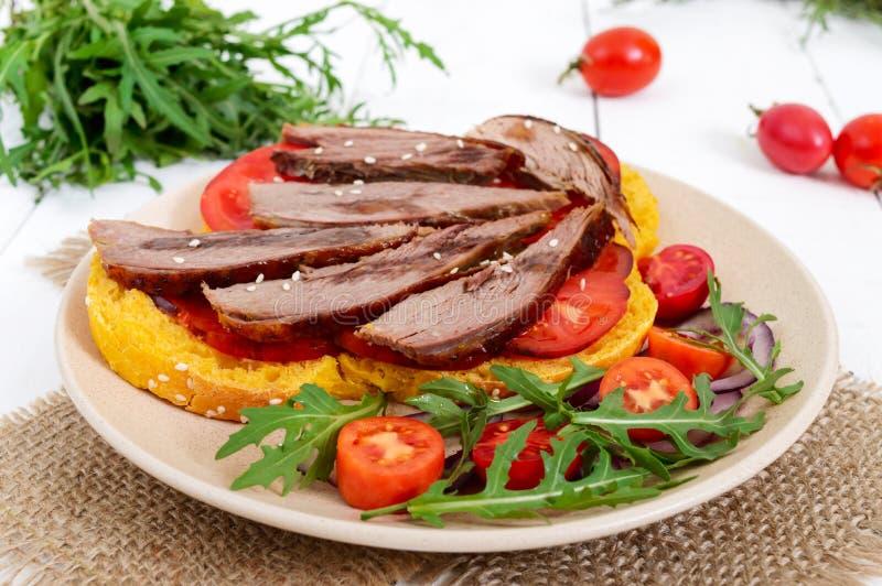 Bocadillos útiles: pecho del ganso en el pan de la calabaza, ensalada de los tomates fotografía de archivo