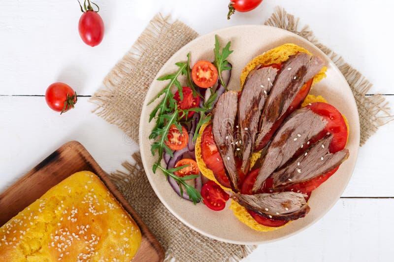 Bocadillos útiles: pecho del ganso en el pan de la calabaza, ensalada de los tomates, arugula, cebollas rojas imagenes de archivo