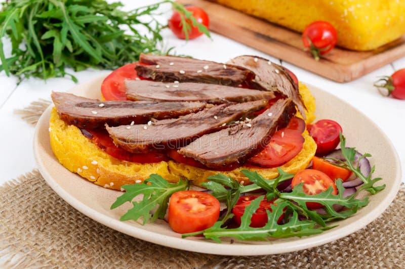 Bocadillos útiles: pecho del ganso en el pan de la calabaza, ensalada de los tomates, arugula, cebollas rojas foto de archivo libre de regalías