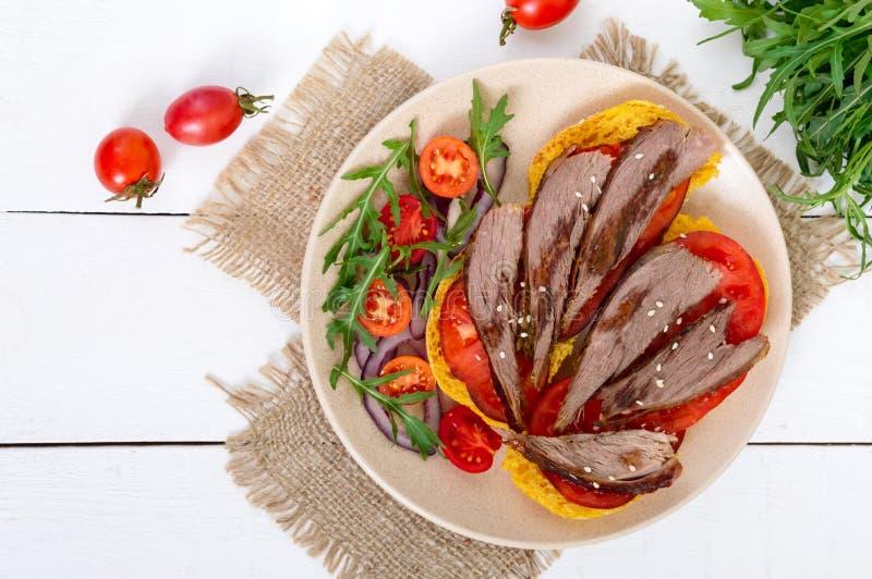 Bocadillos útiles: pecho del ganso en el pan de la calabaza, ensalada de los tomates, arugula, cebollas rojas fotografía de archivo