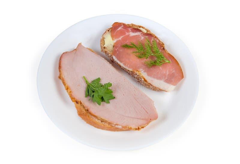 Bocadillos abiertos con cerdo ahumado y curado cocinado en plato fotos de archivo libres de regalías