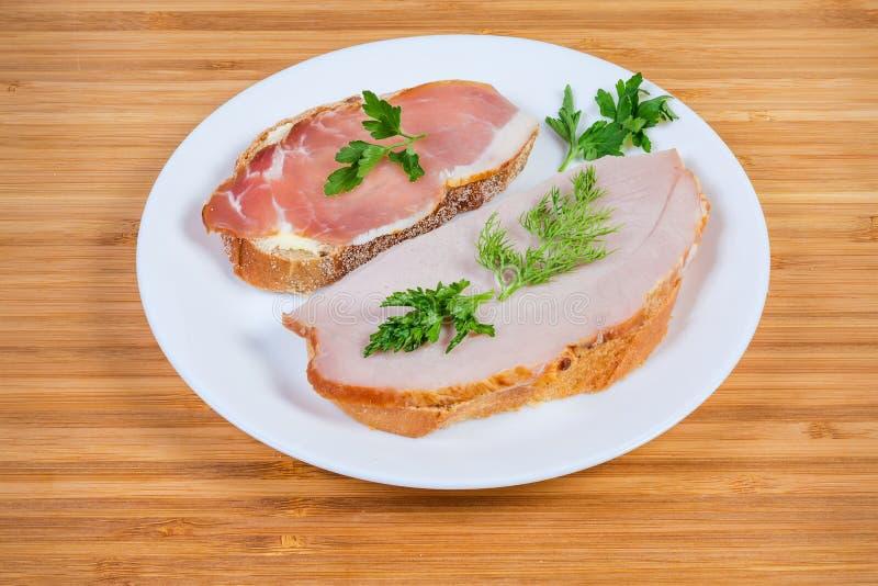Bocadillos abiertos con cerdo ahumado y curado cocinado en plato imagenes de archivo