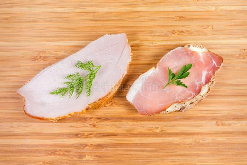Bocadillos abiertos con cerdo ahumado y curado cocinado con verdes fotos de archivo