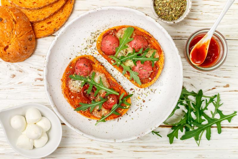 Bocadillos abiertos hechos en casa con la salchicha, el queso de la mozzarella y el arugula fresco imagen de archivo libre de regalías