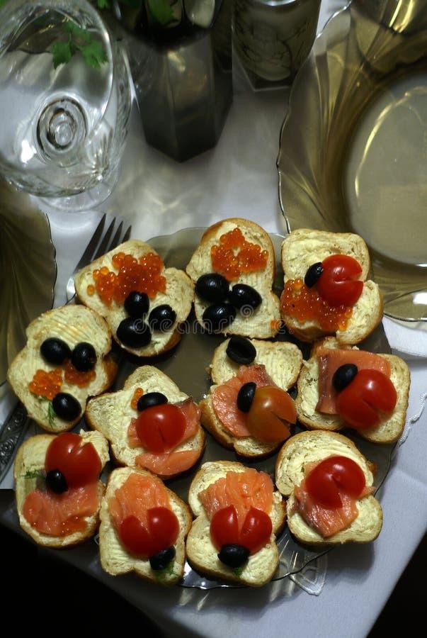 Bocadillos con el caviar rojo, los pescados rojos y las aceitunas imagenes de archivo