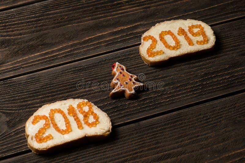 Bocadillos con el caviar rojo 2018 y 2019 en diversas líneas con el pequeño pino-árbol del juguete en medio fotos de archivo