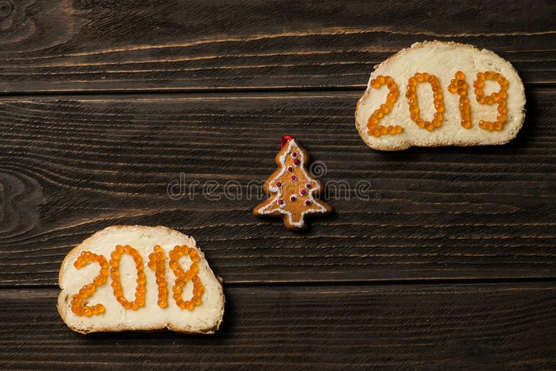 Bocadillos con el caviar rojo 2018 y 2019 en diversas líneas con el pequeño pino-árbol del juguete en medio imagen de archivo libre de regalías