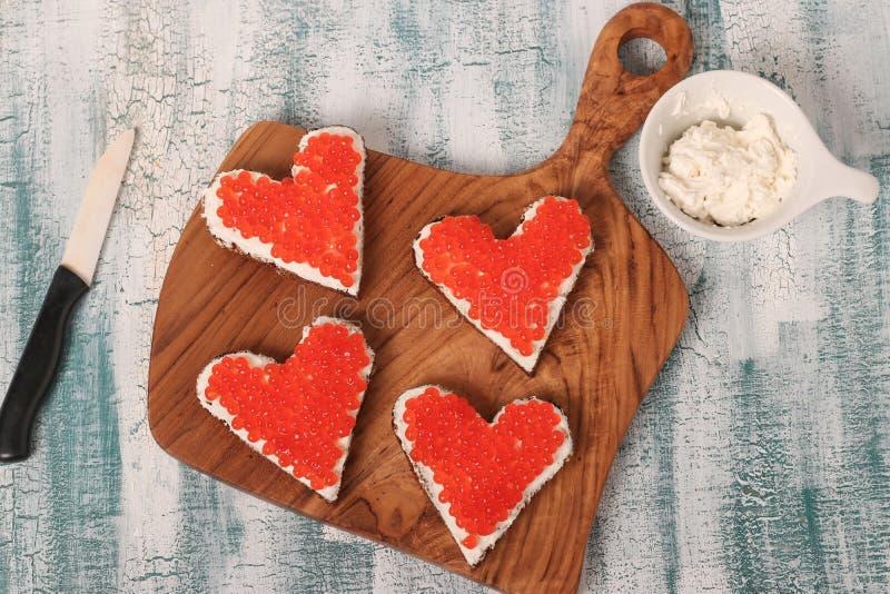 Bocadillos con el caviar y el queso cremoso rojos en la forma de un corazón para el día de tarjeta del día de San Valentín foto de archivo