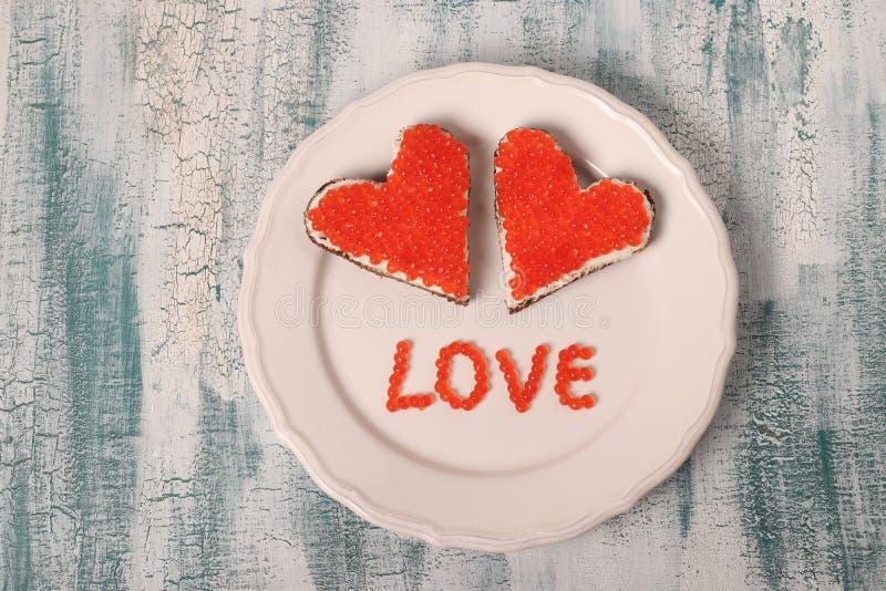 Bocadillos con el caviar y el queso cremoso rojos en la forma de un corazón para el día de tarjeta del día de San Valentín imagenes de archivo