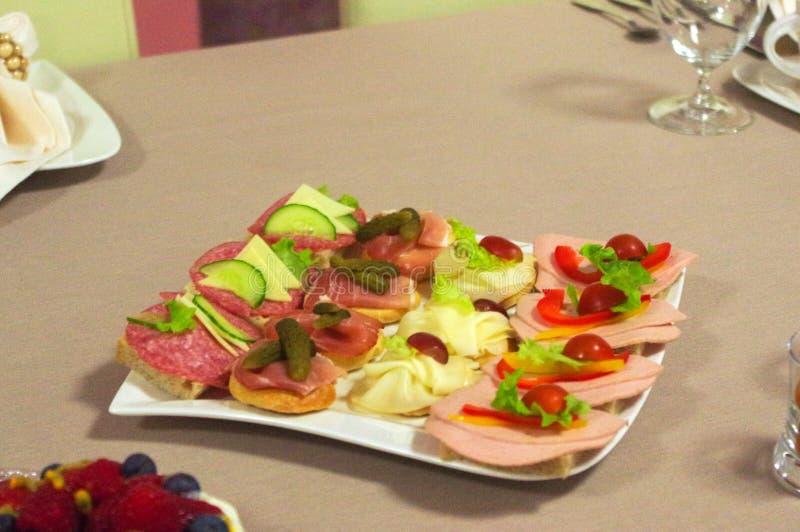 Bocadillos con el queso y la salchicha, sistema del aperitivo, carne, verduras, pan en la placa imágenes de archivo libres de regalías