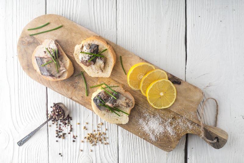 Bocadillos con las sardinas en una tabla de cortar imagen de archivo
