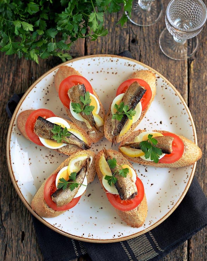 Bocadillos con los espadines, el tomate, el huevo y el limón en el pan del salvado foto de archivo