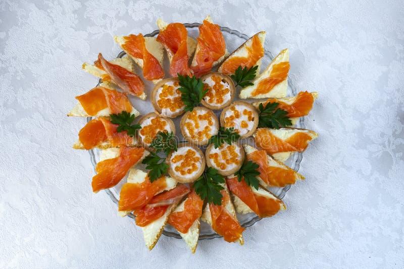 Bocadillos con los pescados y el caviar rojos en un primer de la placa imagen de archivo