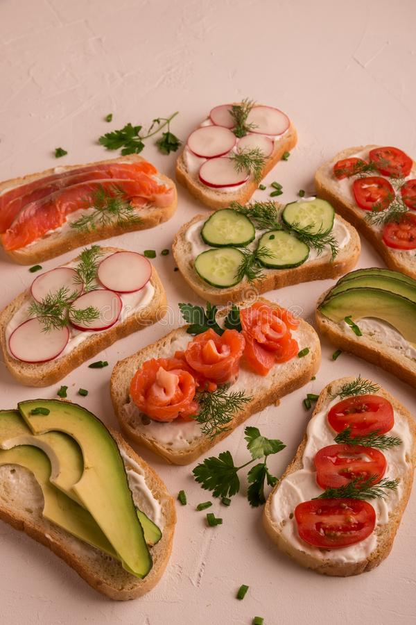 Bocadillos con los salmones, el pepino, los tomates, los aguacates y los verdes, verdura cortada imagen de archivo libre de regalías