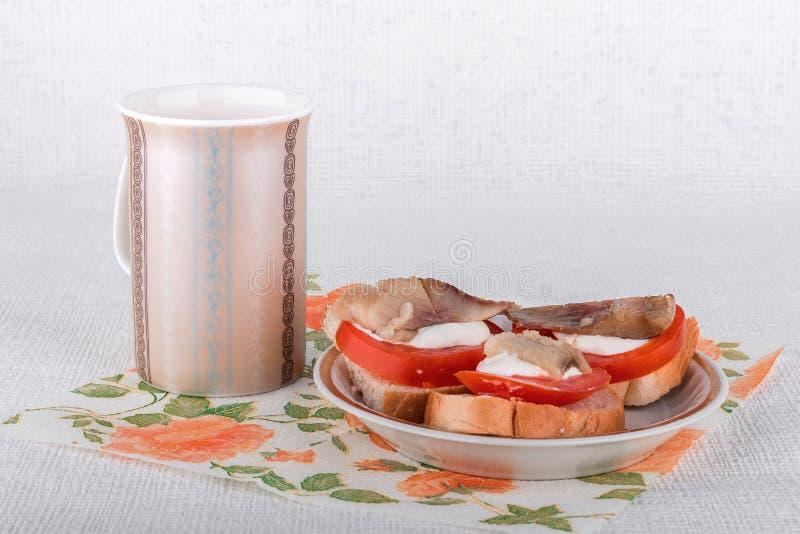 Bocadillos con los tomates y los arenques conservados en vinagre foto de archivo