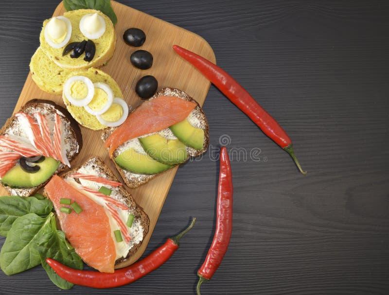 Bocadillos con mantequilla y pescados en la tabla imagen de archivo