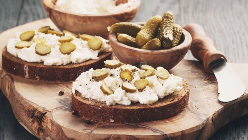 Bocadillos con pan de centeno, queso cremoso y pepinos adobados foto de archivo