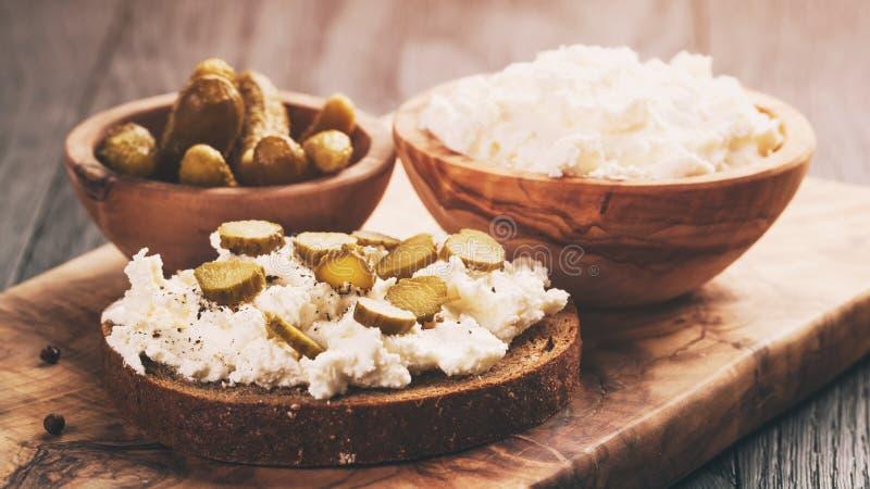 Bocadillos con pan de centeno, queso cremoso y pepinos adobados fotos de archivo