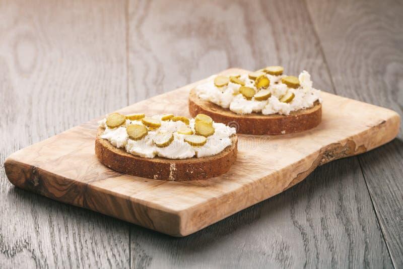Bocadillos con pan de centeno, queso cremoso y pepinos adobados imagen de archivo libre de regalías