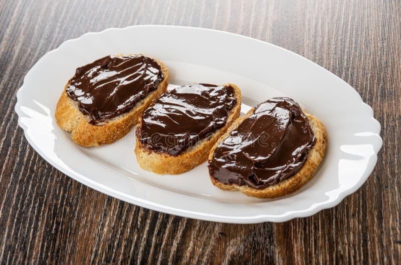 Bocadillos con queso derretido chocolate en plato en la tabla imagen de archivo