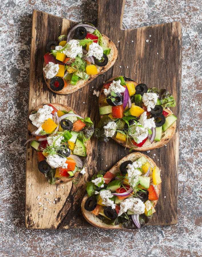 Bocadillos con queso Feta, tomates, pepinos y aceitunas Estilo griego del bruschetta de la ensalada en una tabla de cortar rústic fotos de archivo libres de regalías