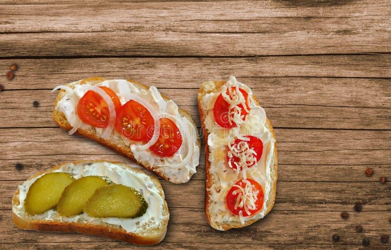 Bocadillos con queso, tomates de cereza y pepinos con goma del requesón en una tabla de madera fotos de archivo