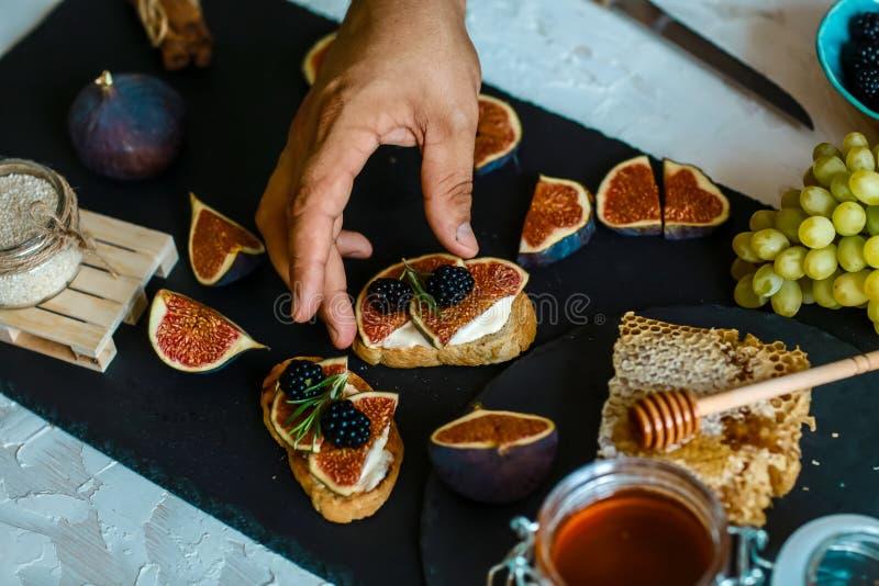 Bocadillos con ricotta, higos frescos, las nueces y la miel en tablero rústico de la pizarra Visión superior Desayuno, foto de la fotos de archivo