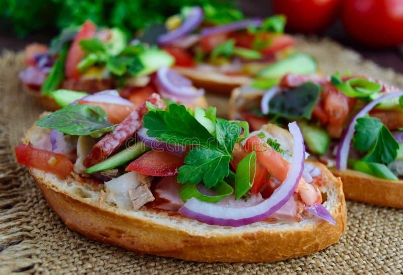 Bocadillos con verdes, tomates, carne, salami en el pan curruscante foto de archivo