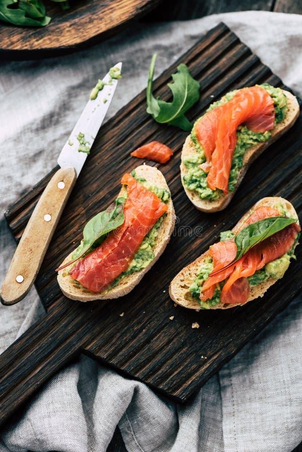 Bocadillos de color salmón de la tostada del aguacate foto de archivo