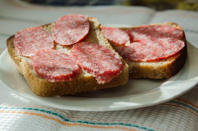 Bocadillos del pan negro con mentiras ahumadas de la salchicha en una placa foto de archivo