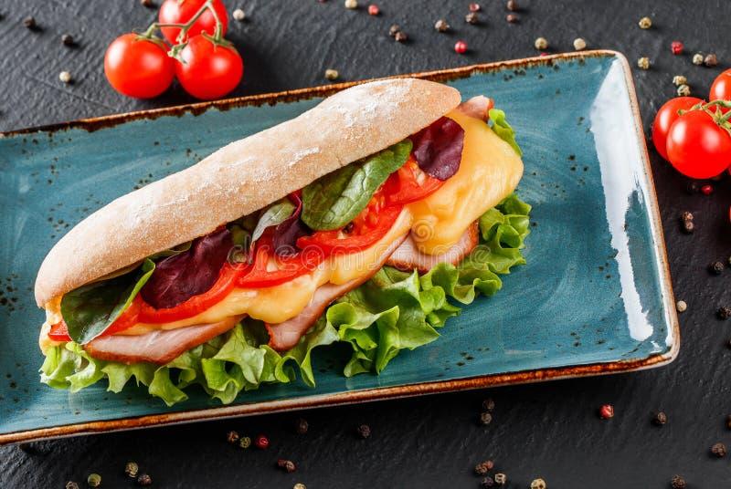 Bocadillos frescos con el jamón, queso, tocino, tomates, lechuga en placa en fondo de piedra oscuro Almuerzo sano imágenes de archivo libres de regalías