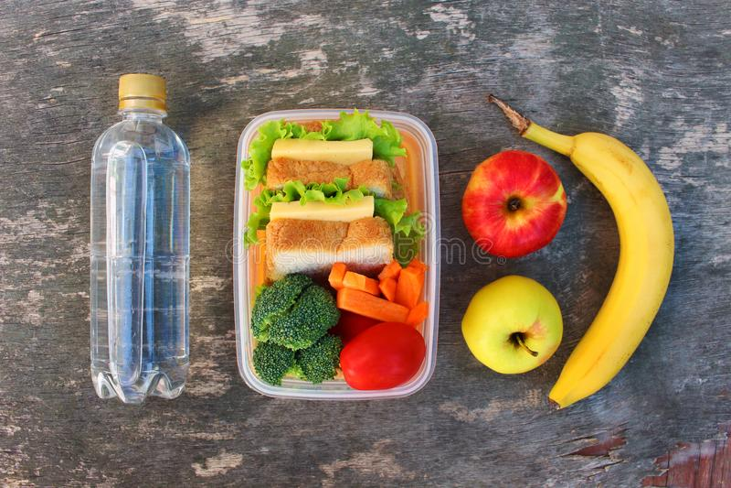 Bocadillos, frutas y verduras en la caja de la comida, agua foto de archivo libre de regalías