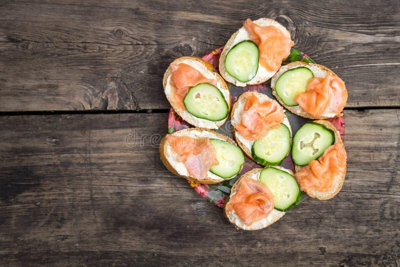 Bocadillos hechos en casa con los salmones y el pepino rosados imagenes de archivo
