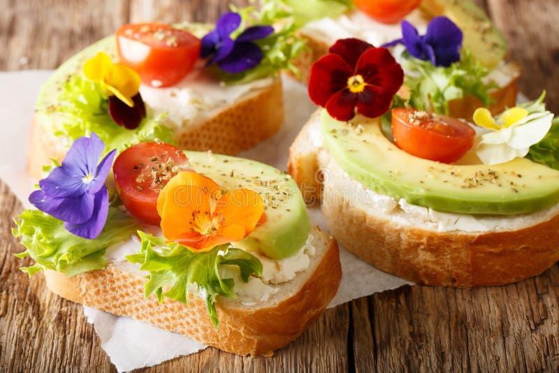 Bocadillos hermosos con el aguacate, tomates, flores comestibles de v imagenes de archivo