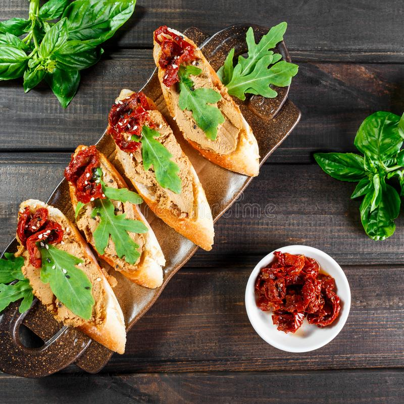 Bocadillos italianos - bruschetta con la coronilla de la carne, el arugula, el tomate secado al sol y las semillas en el pan del  imagen de archivo