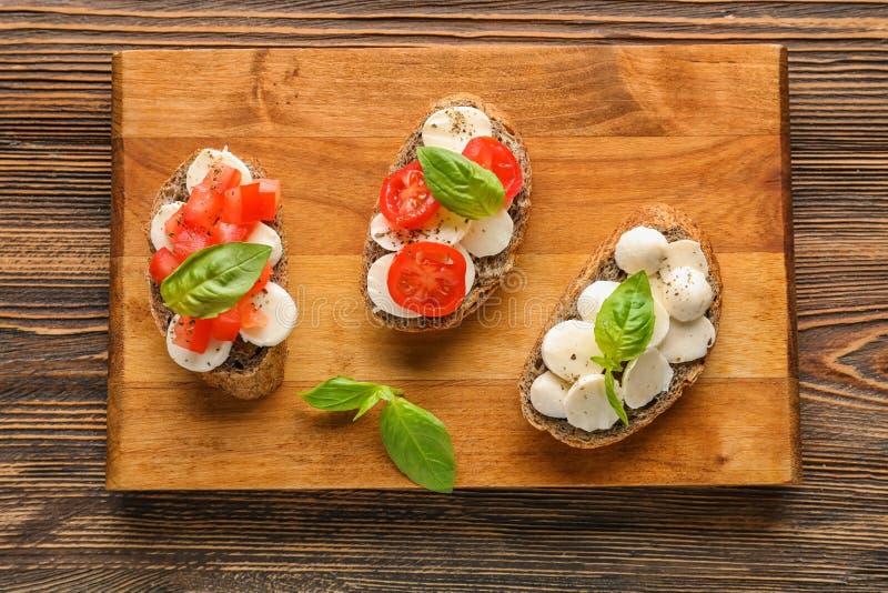 Bocadillos sabrosos con la mozzarella, el tomate y la albahaca en el tablero de madera imagen de archivo