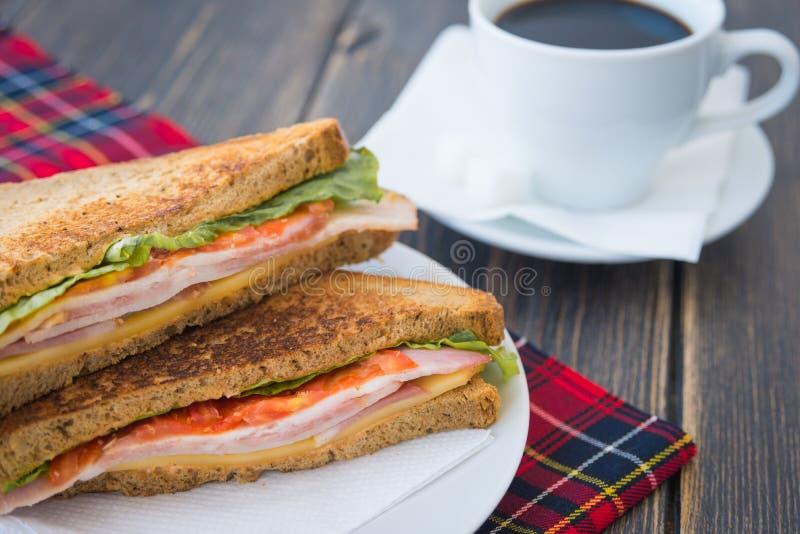 Bocadillos sabrosos con queso y tocino y una taza de café express foto de archivo