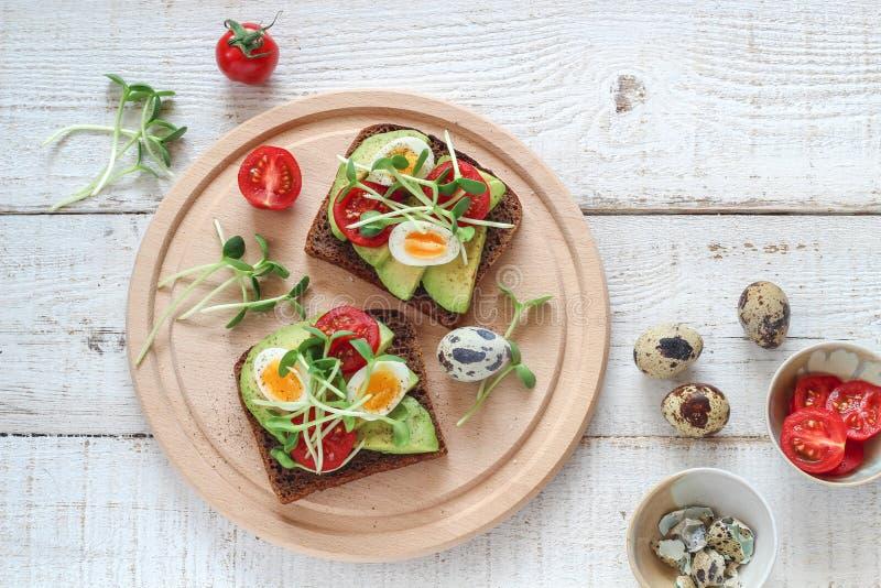 Bocadillos sanos con el aguacate, el tomate, los huevos de codornices y los brotes micro de los verdes de los girasoles fotos de archivo