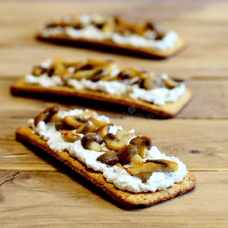 Bocadillos sanos en una tabla de madera Bocadillos abiertos con queso suave y setas en el pan quebradizo Aperitivo vegetariano sa foto de archivo