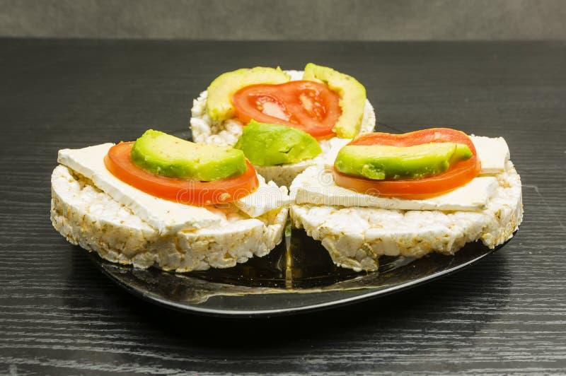 Bocadillos sanos y dietéticos - torta de arroz con el queso, tomate a imagen de archivo